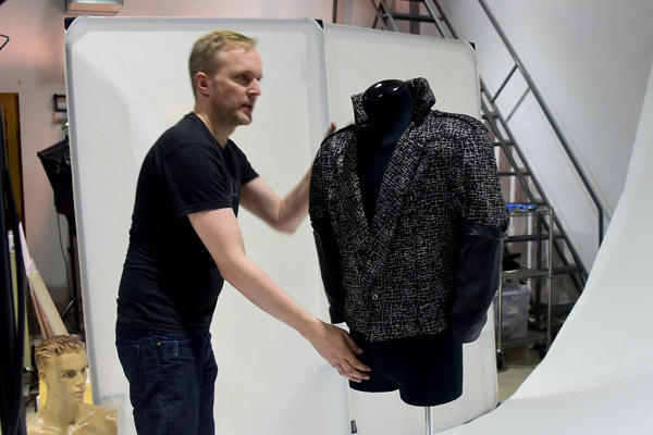 """Raymond Janis from Profiles in History adjusts the jacket worn by Prince in the 1984  film """"Purple Rain"""" is displayed on April 29, 2016 in Calabasas, California, ahead of its auction on June 29, 2016 from California-based auction house Profiles in History. An iconic jacket worn by Prince in the 1984 film """"Purple Rain"""" will be auctioned in Los Angeles in June, auction house Profiles in History said. / AFP / FREDERIC J. BROWN"""