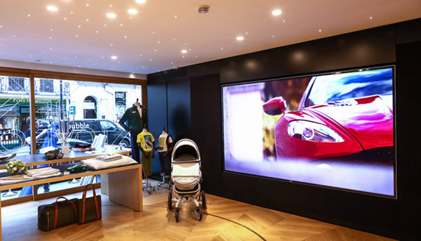 A giant 120-inch widescreen television displays an advert during the launch event for the 'Aston Martin at No. 8 Dover Street' luxury brand experience boutique by Aston Martin Lagonda Ltd. in London, U.K., on Thursday, Sept. 1, 2016. The British marque is seeking to broaden its appeal with the world's wealthy by becoming more than a maker of vehicles like the DB11 sports car. Photographer: Chris Ratcliffe/Bloomberg